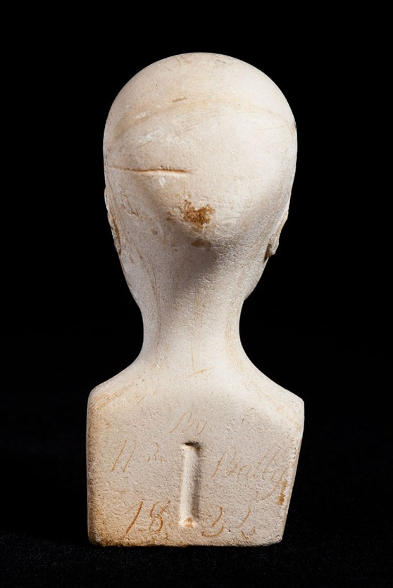 Reverse view of miniature phrenology bust showing inscription