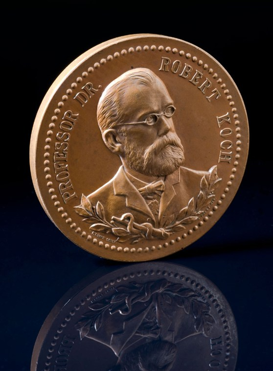 Photograph of a circular bronze medal showing a portrait image of Robert Koch