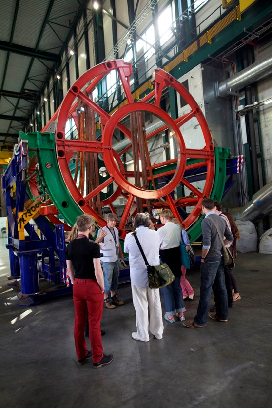 Several visitors listen to a CERN staff member talk in front of a large circular metal girder construction