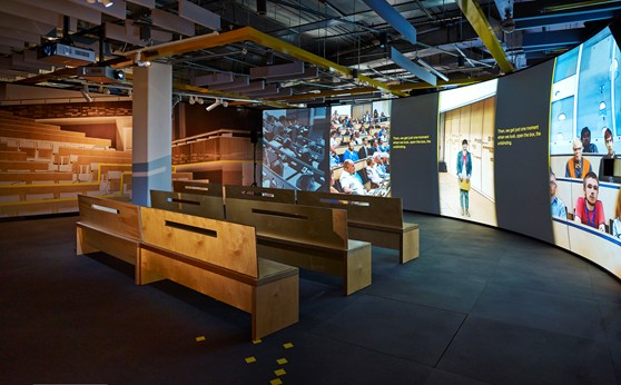 Part of the Collider exhibition showing several wooden benches in front of a large television screen showing the exhibition introductory video