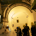 Several visitors in hard hats stand in a large underground dimly lit room at the entrance to a large circular tunnel
