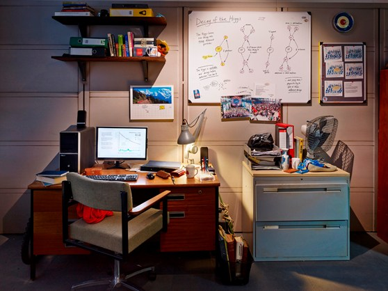 Recreation of a CERN student office in the Collider exhibition, with a cluttered desk, filing cabinet and whiteboard