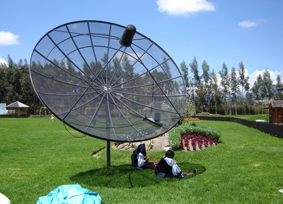Two Ecuadorian women adapt technology to their own lives by creating a sunshade out of a satellite dish