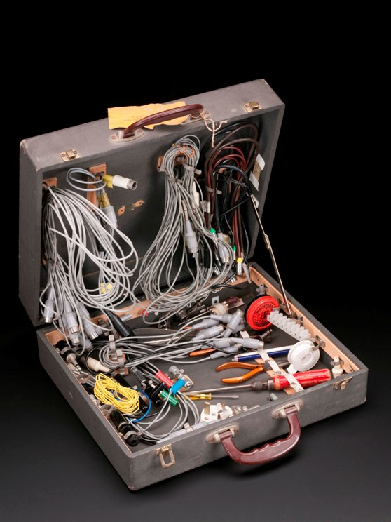 A suitcase containing a variety of small electrical tools, electrical items and wires