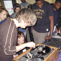 Several members of the National Youth Theatre watch Aleks Kolkowski use an old analogue piece of audio recording kit