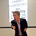 Colour photograph of Mat Fraser singing into the microphone during a performance of Cabinet of Curiosities