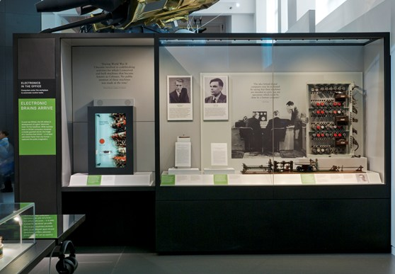 Colour photograph of a display case on computing in the Information Age exhibition showingpictures of early computer specialists a valve from an early computer and a part of the Manchester Mark 1 machine