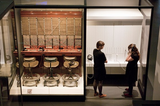 Colour photograph from a high elevation of an old genuine manual telephone exchange desk and two visitors using the adjacent switchboard demonstration console