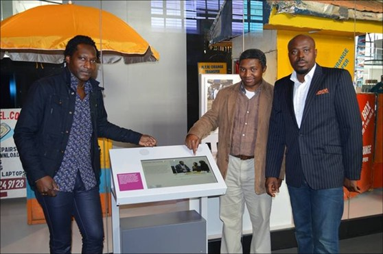 Colour photograph of three particpants from Cameroon in the Information Age gallery