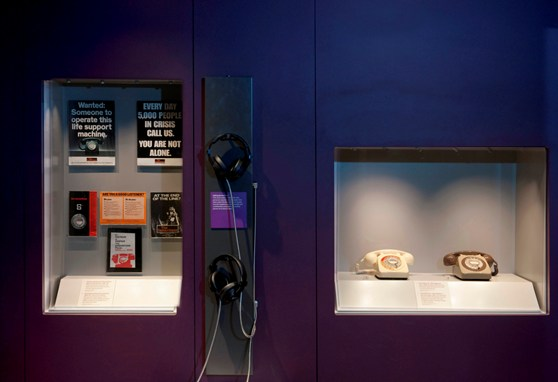 Colour photograph of the empathetic ear display in Information Age showing Samaritans posters and landline telephones