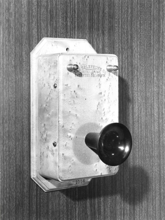 Black and white photograph of a wall mounted telephone from the late 1800s