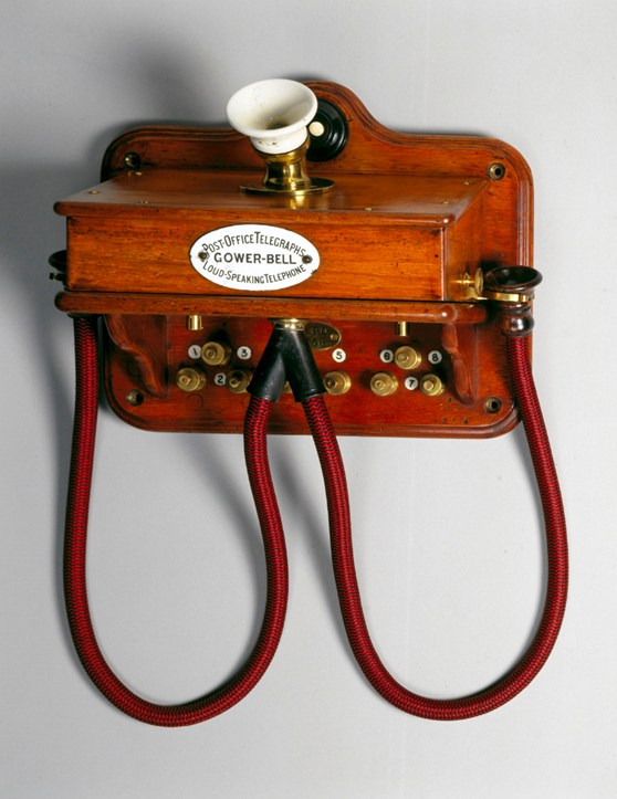 Colour photograph of a wall mounted wooden telephone with two earpieces from the 1880s
