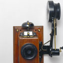 Colour photograph of a wall mounted telephone that uses an Edison chalk receiver from the early 1900s