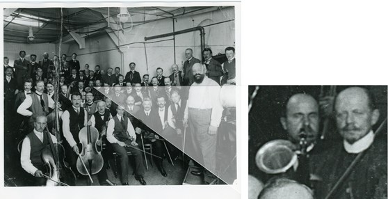 Black and white photograph of the Berlin Philharmonic Orchestra with their instruments in a Gramophone recording studio with a close up of the horn of a stroh violin