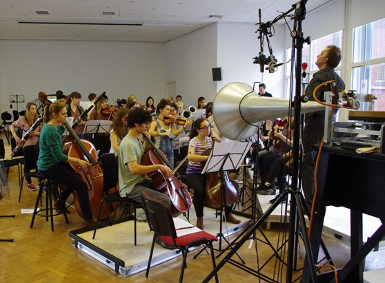 Colour photograph of the cellos and basses part of the royal college of music chamber orchestra recording music to wax discs