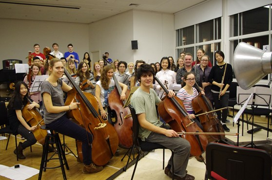 Colour photograph of the RCM chamber orchestra and conductor looking to camera