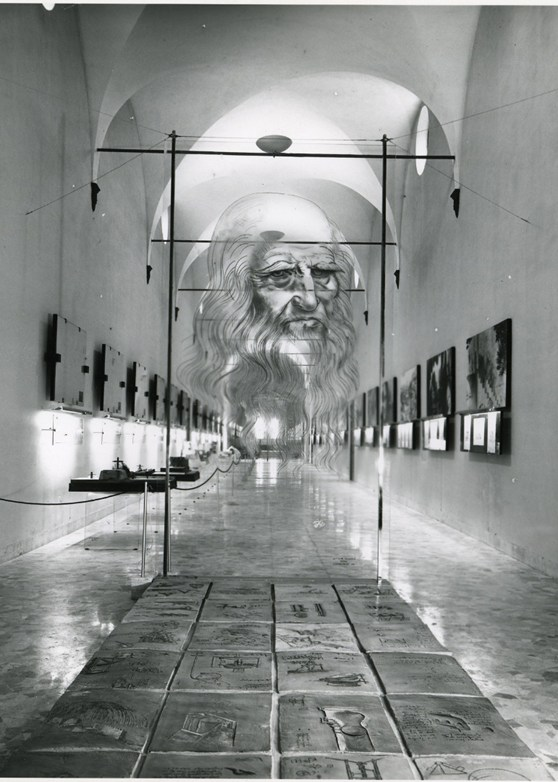 Black and white photograph of a corridor in which are displayed a number of leonardo models paintings and information plaques