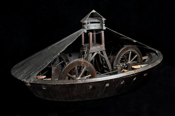 Colour photograph of a wooden model of a covered war chariot with a cut out section showing interior detail
