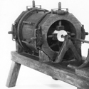 Black and white photograph of a working model of a wooden machine for boring holes in wood