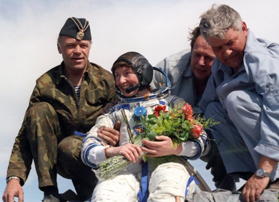 Colour photograph of Helen Sharman female space tourist in a space suit smiling and holding flowers as she is helped down from a module