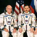 Colour photograph of three seated astronauts in space suits one of which is Dennis Tito the first space tourist