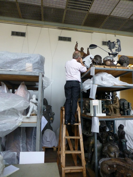 Colour photograph of Doug Millard curator at the Science Museum examining sculptures at the GTG sculpture stores