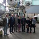 Colour photograph of the Science Museum delegation inside a storage warehouse for old soviet space exploration technology
