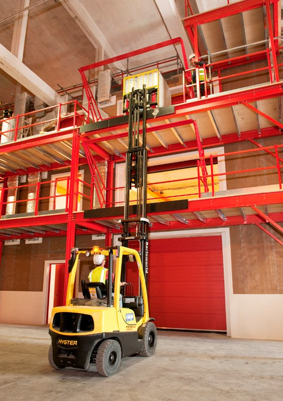 Colour photograph showing transportation of objects to upper storeys of the structure using a forklift truck