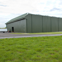 Colour photograph of a large corrugated metal storage hangar