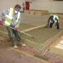 Colour photograph of workers precasting hempcrete panels for use in the storage building