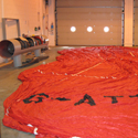 Colour photograph of a large deflated hot air balloon canvas spread on the floor of a warehouse