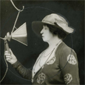 Black and white photograph of Dame Ellie Melba singing into an early microphone from 1920
