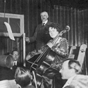 Black and white photograph of Elgar conducting a symphony orchestra with Beatrice Harrison on Cello recording into early microphones