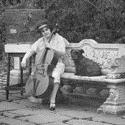 Black and white photograph of Beatrice Harrison playing the cello in her garden seated next to a dog and surrounded by pet birds in cages