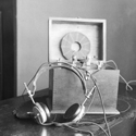 Black and white photograph of an early audio listening device with attached headphones