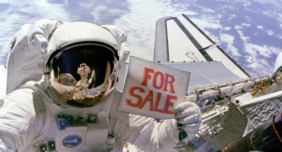 Colour photograph of an astronaut in space floating above a spacecraft and holding up a sign which reads for sale