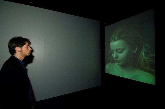 Colour photograph of a museum visitor looking at a video projection of a woman sleeping