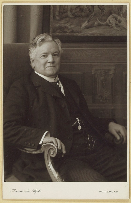 Black and white photograph of a middle aged male doctor sat in an ornate wooden chair