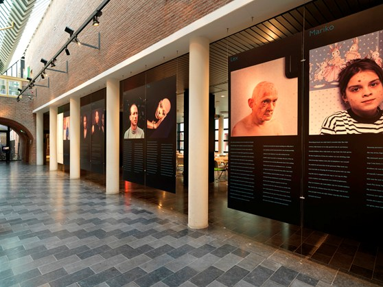 Colour photograph of a modern gallery showing large images of people afflicted with disease