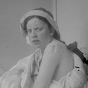 Old black and white photograph of a young woman as a patient in a hospital for treating sufferers of tuberculosis
