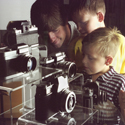 Colour photograph of a man and his two boys looking into a glass case display of cameras