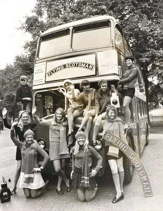 Black and white publicity photograph of a double decker bus with Flying Scotsman printed on the front and a number of young women surrounding the bus