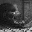 Black and white photograph of the Flying Scotsman steam train emerging from a tunnel. Anti diesel train graffiti is visible on the brickwork