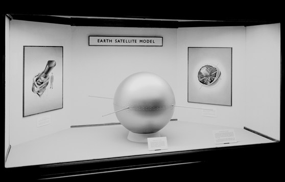 Black and white photograph of a model of an early satellite on display as part of an exhibition