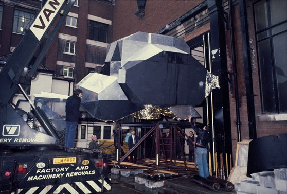 Colour photograph of a moon landing unit being winched into a warehouse at the Science Museum London