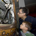 Colour photograph of a man and a boy looking inside the Apollo landing craft on display at the Science Museum London