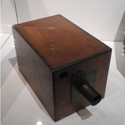 Colour photograph of an early wooden box camera on display in a glass case