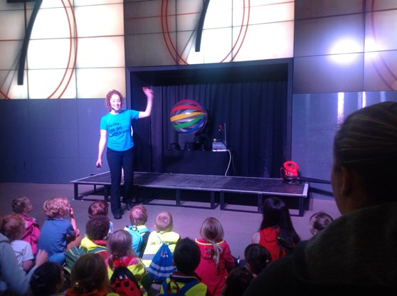 Colour photograph of a science museum explainer giving a demonstration to school children