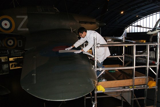Colour photograph of a conservator repairing a tear on the wing of a Hawker Hurricane aircraft