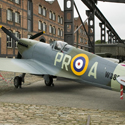 Colour photograph of a renovated Spitfire aircraft outside the Museum of Science and Industry